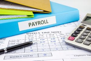 Binder labeled PAYROLL next to Time Card and Calculator